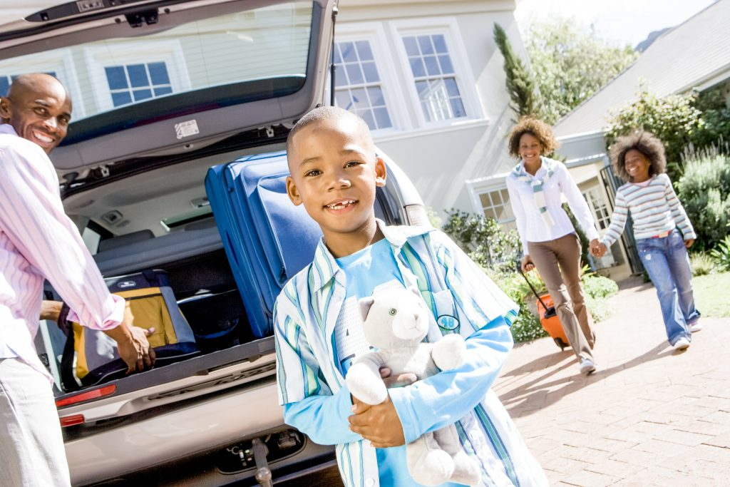 Family packing up vehicle to travel traveling with an infant